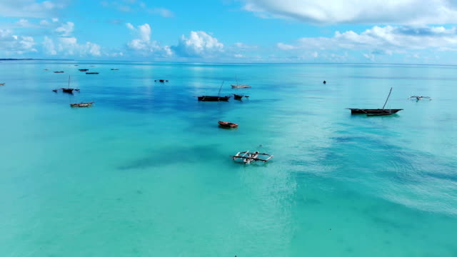 Aerial-view-of-a-fisherman-sails-on-a-wooden-boat-on-clear-blue-water-along-a-tropical-exotic-beach-in-Africa