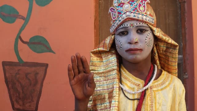 Young-girl-dressed-as-a-goddess-with-painted-face-gives-blessings-looking-towards-the-camera-with-one-hand-raised-handheld
