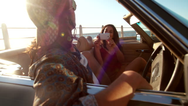 Happy-young-hipster-couple-taking-pictures-in-a-convertible