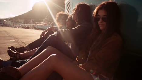 Hipster-friends-resting-out-of-their-van-at-sunset