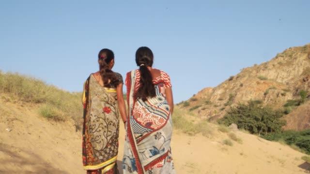 Ladies-holding-hand-walking-talking-desert-Rajasthani-traditional-dress-summer-hot-sun-sand-stone-handheld-bonding-love-share-from-back-wide-shot-medium-follow-stabilized-gimbal-hill-sari-dress