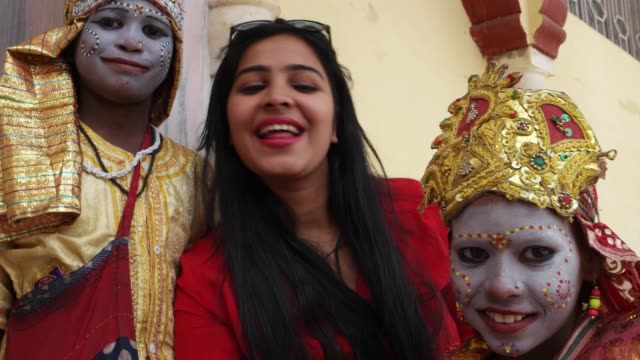 POV-of-a-camera-taking-selfies-of-a-urban-tourist-posing-with-two-child-actors-in-goddess-make-up-with-a-smart-mobile-phone-camera-handheld