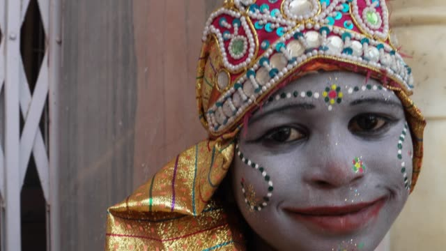 Close-up-handheld-of-a-female-child-dressed-as-a-Hindu-God-wit-makeup-crown-costumes-and-gives-divine-blessings