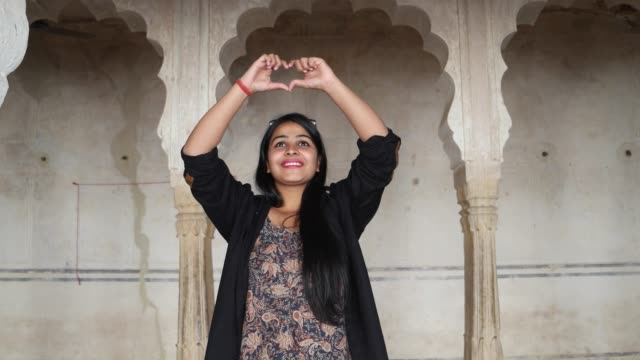 Happy-woman-walks-into-frame-and-admires-an-ancient-Indian-temple-moves-her-hands-over-her-head-looks-to-camera-makes-heart-sign-with-fingers-inside-building-interior-handheld-follows-smiles-fun-love