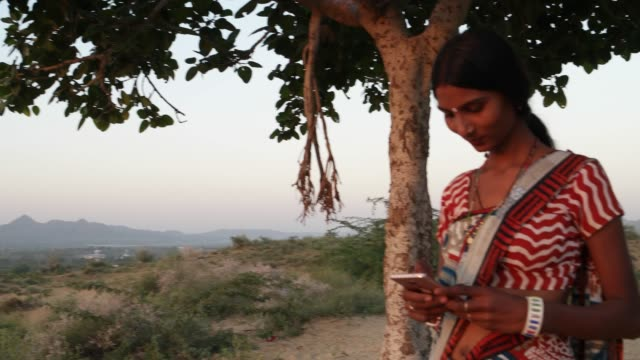 Tiro-de-mano-de-mujer-textos-mensaje-compartir-foto-sonrisas-video-móvil-comunica-dispositivo-conectividad-señal-wireless-al-atardecer-en-la-naturaleza-al-aire-libre-Cerro-caliente-hora-mágica-de-verano-hermoso-ángulo-bajo