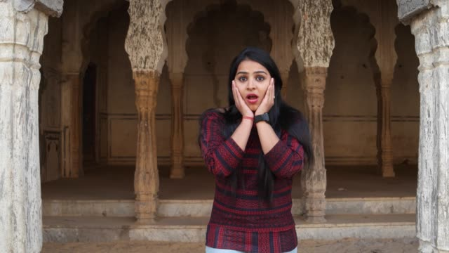 Handheld-shot-of-woman-pissed-angry-bad-mood-smart-watch-late-nods-surprised-smiles-joke-kidding-joy-hands-on-face-looks-at-camera-in-old-ancient-Hindu-temple-facade-complex-holy-city-move-to-frame