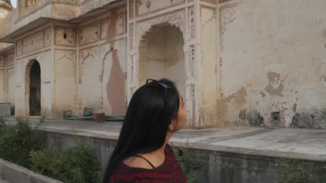 Tiro-mano-de-mujer-turista-frente-a-hindú-Templo-tomando-selfie-foto-video-en-su-teléfono-inteligente-móvil-feliz-comparte-fachada-arquitectura-antigua-fortaleza-religiosa-Santo-Castillo-Palacio-Rajasthani