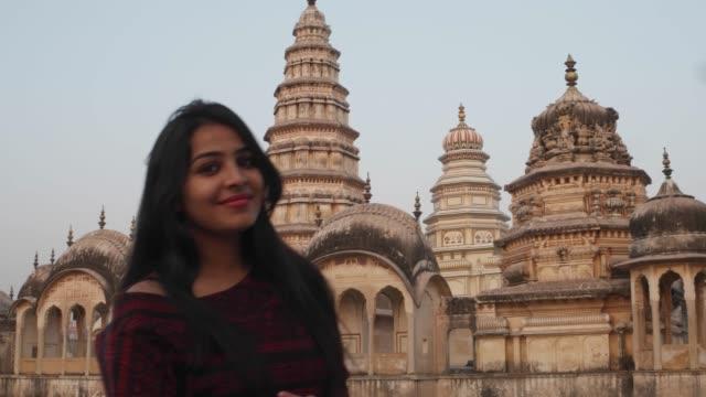 Mujer-delante-panorámica-templo-ornamentado-atractivo-fuerte-complejo-del-Palacio-de-un-nivel-más-alto-de-mirador-tomando-foto-selfie-en-teléfono-móvil-cámara-turismo-amor-masivo-religioso-hindú-mano-pov