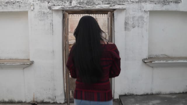 Junge-Frau-betritt-und-verlässt-ein-altes-Gebäude-Eingang-mit-gefalteten-Händen-verbunden-Namaste-eine-traditionelle-indische-Begrüßung-für-lacht-lächelt-Respektpunkte-Hände-Youngster-Wellen-Joviale-älteren-handheld