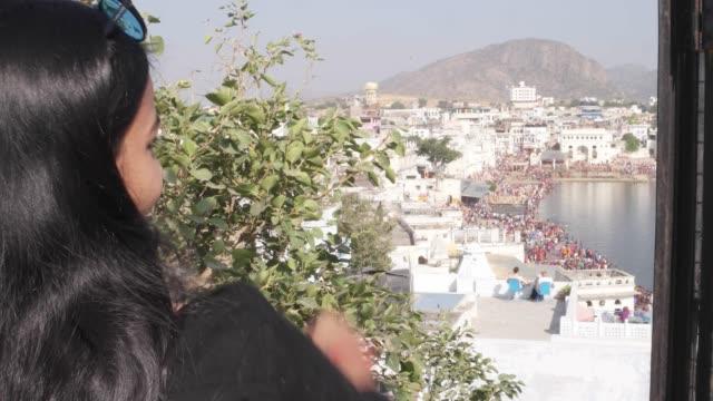 Mujer-mano-toma-selfie-foto-vídeo-con-su-dispositivo-celular-móvil-desde-un-punto-de-vista-de-vista-panorámica-de-Santo-lago-de-Pushkar-una-ciudad-sagrada-para-el-festival-mela-de-peregrinos-hindúes-templos-de-ghats-de-baño