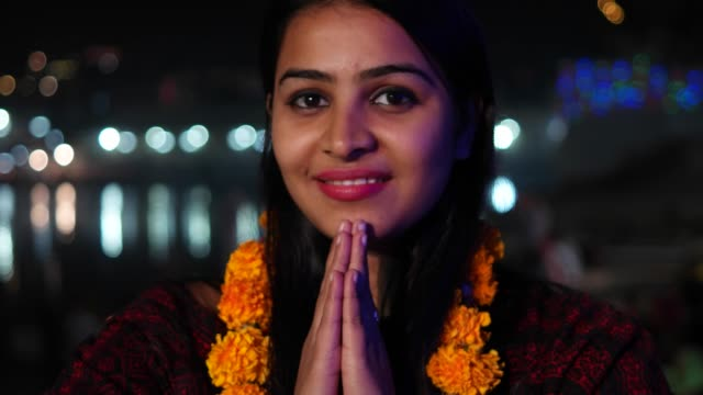 Beautiful-young-woman-hands-joined-in-namaste-greets-with-orange-marigold-flower-garland-on-her-neck-offers-prayers-worship-God-Goddess-hands-welcomes-smiles-glowing-respect-believer-religion-handheld