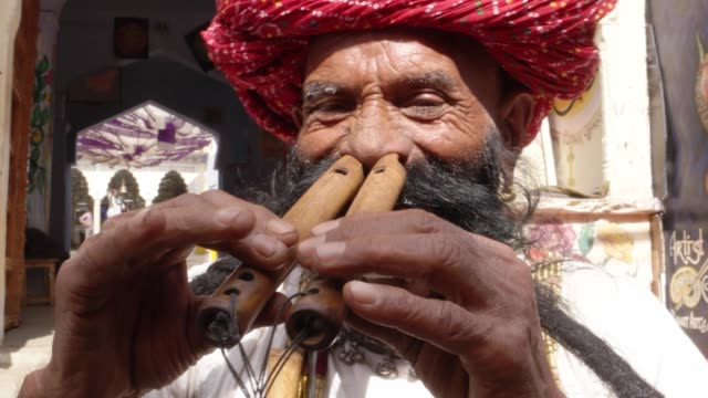 Hand-held-CU-Rajasthani-elderly-male-plays-the-flute-with-his-nose-in-front-of-a-painted-temple-archway-with-big-moustache-wearing-traditional-attire
