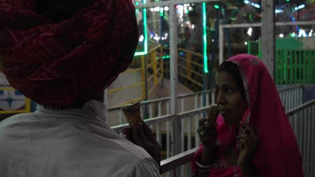 Pareja-India-comiendo-helado-en-vestidos-tradicionales-en-la-Pushkar-Mela-un-carnaval-de-Rajasthán-la-India