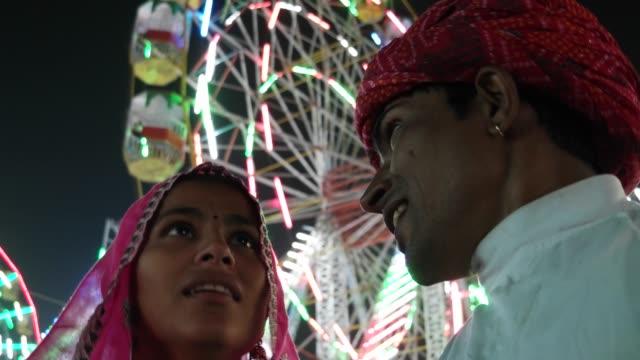 Indian-traditional-couple-talking-in-pink-sari-and-red-turban-at-Pushkar-Mela-a-carnival-of-Rajasthan-India