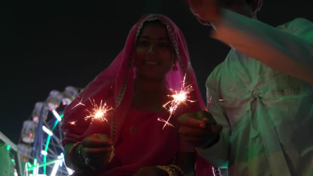 Indian-couple-in-traditional-dress-with-fire-sparkle-cracker-at-Diwali-Mela-festival-in-India