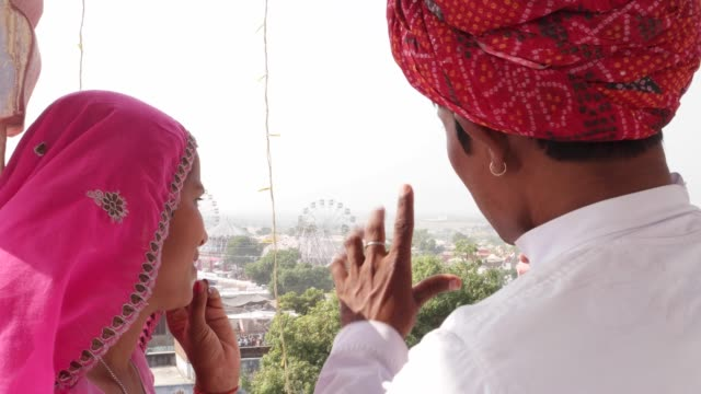handheld-shot-of-Beautiful-girl-and-buy-watching-a-carnival-from-a-rooftop-and-talking-India