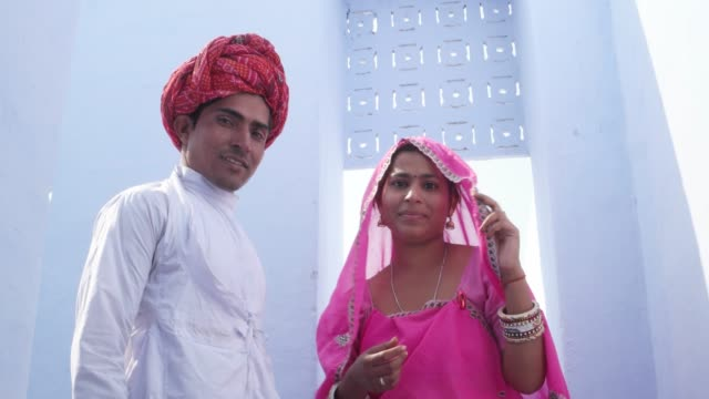 Woman-in-pink-sari-and-man-in-red-turban-with-light-blue-background-pose-for-camera-in-Rajasthan-India