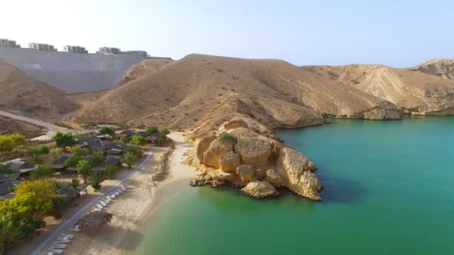 Aerial-view-of-Muscat-bay-dive-resort-day-trip-and-relaxing-area-crystal-clear-water-of-Indian-Ocean-beach-and-blue-lagoon-Oman-sultanate-on-Arabian-Peninsula-4k-UHD