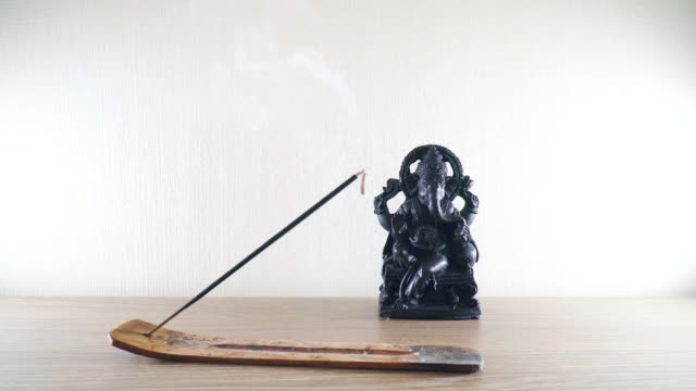 Burning-incense-stick-on-a-background-Ganesh-statues-in-the-Buddhist-temple