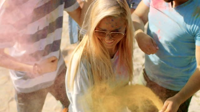 High-Angle-Shot-of-a-Blonde-Girl-Throwing-Colorful-Powder-in-the-Crowd-Amidst-Hindu-Holi-Festival-Celebrations-They-Have-Enormous-Fun-on-this-Sunny-Day-