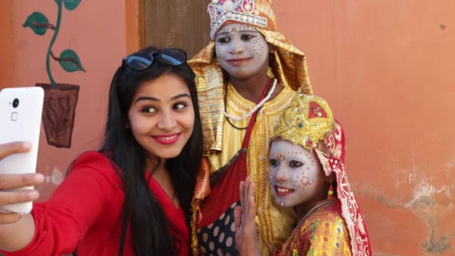 Handheld-shot-of-an-urban-Indian-female-tourists-with-two-females-dressed-as-goddess-taking-selfie-photography-making-video