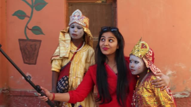 A-tourist-takes-selfies-photo-video-with-two-child-actors-in-goddess-make-up-with-a-smart-mobile-phone-camera-handheld