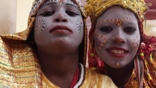 Handheld-closeup-of-two-young-girls-in-an-Indian-town-dressed-as-Goddess-for-alms-and-celebrations-divinity-and-bless-tourists-look-at-camera-and-smile