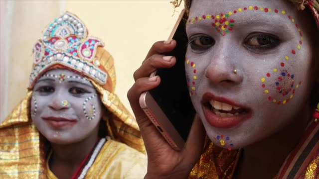 Handheld-close-up-of-young-girls-dressed-as-Hindu-God-talking-communication-technology-on-a-smart-mobile-phone-and-look-at-the-camera-happy-joy-content