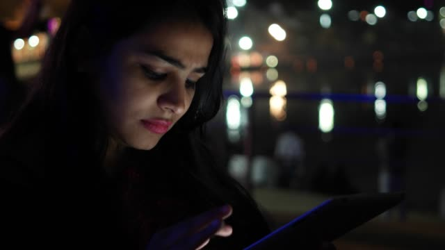 Young-woman-serious-working-on-a-tablet-pad-touch-screen-for-keeping-in-touch-looking-around-information-travel-guide-booking-book-network-surf-internet-with-the-back-drop-of-a-temple-holy-town-lake
