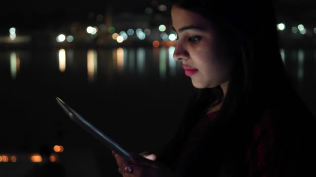 Young-woman-video-chats-talks-smiles-on-tablet-pad-waves-hands-bye-greets-welcomes-touch-screen-information-travel-network-surf-internet-points-at-the-Hindu-temple-holy-town-lake-city-handheld-con-cal