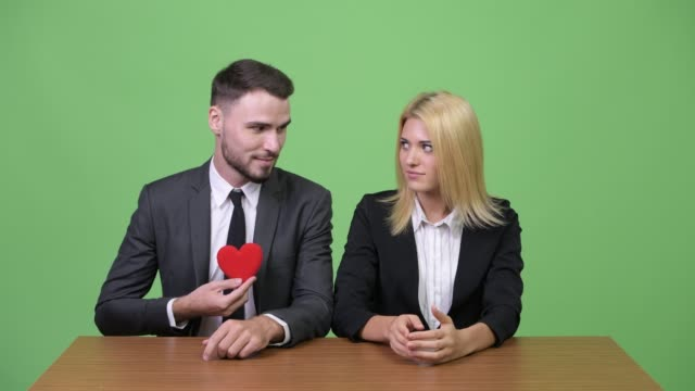 Young-businessman-flirting-with-young-businesswoman-while-working