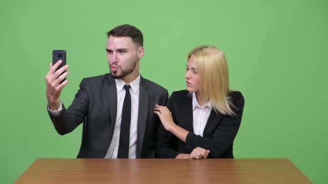 Young-businessman-playing-while-working-with-young-businesswoman-focusing