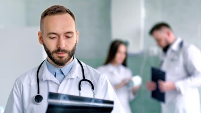 Retrato-de-hombre-masculino-médico-con-estetoscopio-revisión-instantánea-de-rayos-x