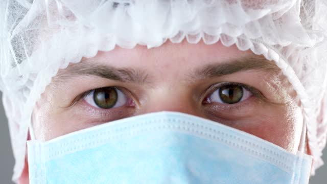 Un-retrato-de-un-médico-o-un-cirujano-en-una-máscara-médica-un-respirador-ojos-marrones-un-gorro-en-un-hospital-o-una-clínica-