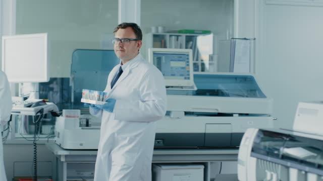 Científico-de-investigación-hombre-camina-a-través-de-laboratorio-con-bandeja-de-tubos-de-ensayo-con-las-muestras-En-el-fondo-las-personas-trabajando-en-laboratorio-con-equipos-innovadores-En-cámara-lenta-