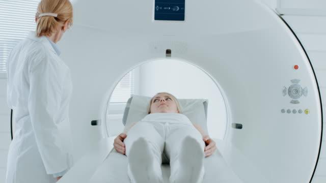 En-el-laboratorio-médico-paciente-femenino-acostado-en-una-cama-de-exploración-de-MRI-o-CT-somete-a-análisis-el-procedimiento-bajo-la-supervisión-de-un-radiólogo-profesional-Paciente-se-mueve-a-través-de-la-máquina-mientras-que-explora-