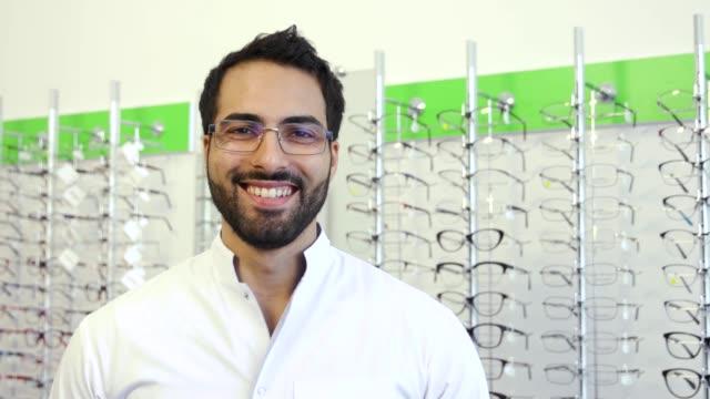 Óptica-médico-junto-a-la-vitrina-con-las-gafas-en-la-tienda-de-gafas