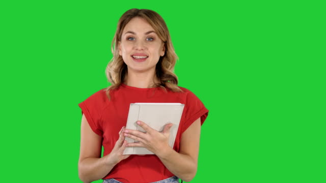 Mujer-presentadora-de-camiseta-rojo-sosteniendo-un-tablet-da-vuelta-páginas-y-hablando-a-la-cámara-en-una-pantalla-verde-Chroma-Key