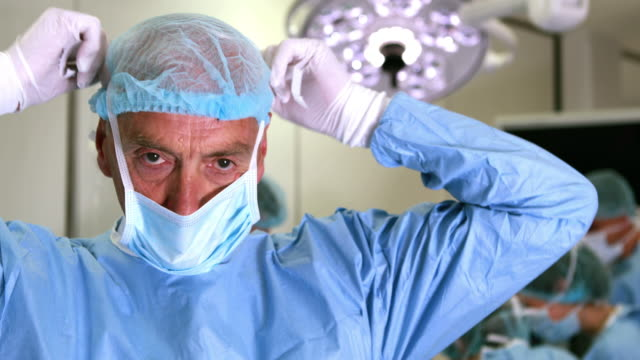 Medical-professor-in-surgical-gear-putting-on-mask