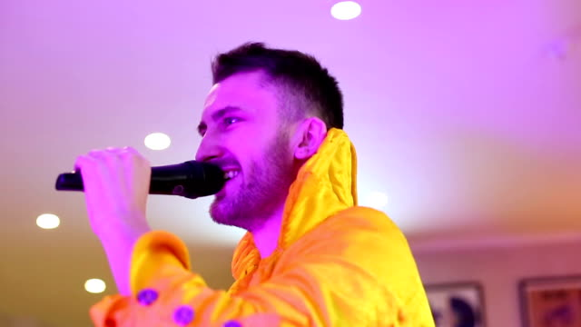 Showman-in-yellow-fashionable-suit-speaks-in-a-microphone-