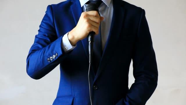 Mann-im-Anzug-halten-und-geben-Sie-ein-Mikrofon-für-eine-Business-Interview-Journalistin-öffentlich-zu-sprechen-Pressekonferenz-MC