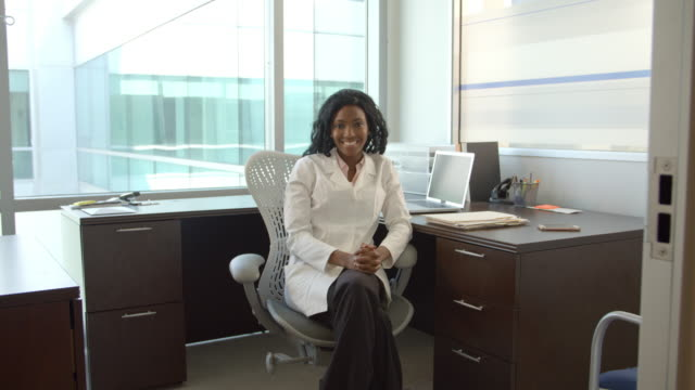 Portrait-Of-Female-Doctor-Working-At-Desk-In-Office