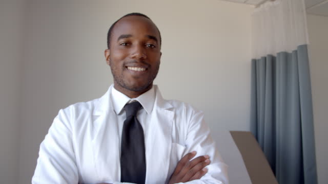 Portrait-Of-Male-Doctor-Wearing-White-Coat-In-Exam-Room