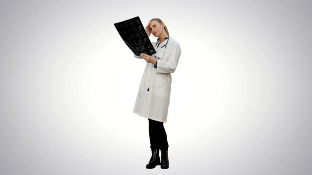 Female-doctor-looking-at-xray-of-human-brain-on-white-background