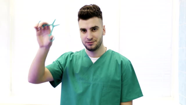 Close-up-of-a-young-doctor-in-medical-suit-shows-clips-(scissors)-