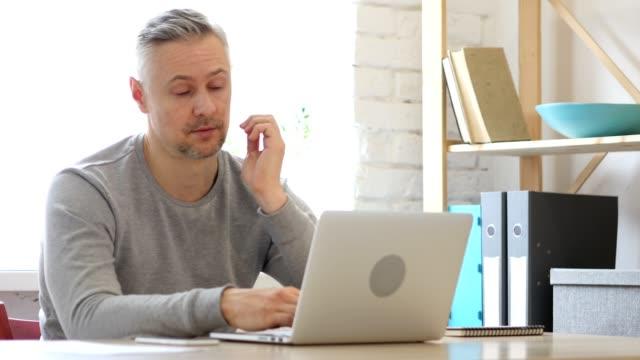 Cansado-en-medio-de-años-hombre-trabajando-en-ordenador-portátil-carga-de-trabajo