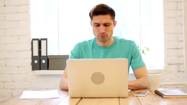 Cansado-joven-hombre-trabajando-en-ordenador-portátil-carga-de-trabajo