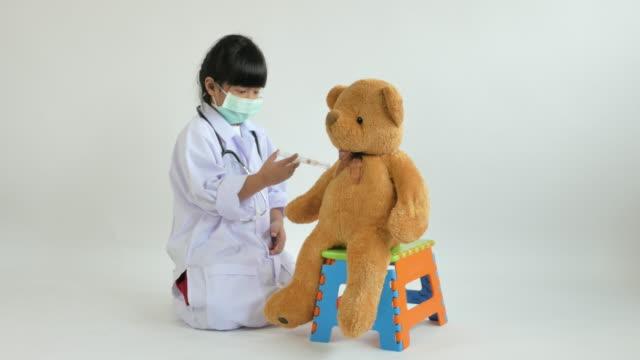 Jugar-a-doctor-con-muñeca-oso-del-niño-Asiático