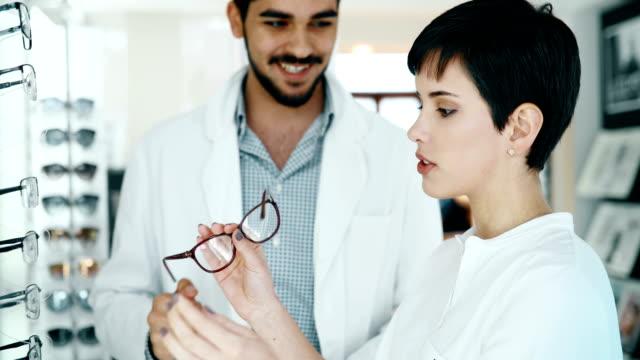 Hermosa-mujer-con-tratar-de-las-lentes-en-la-tienda-de-óptica-optician