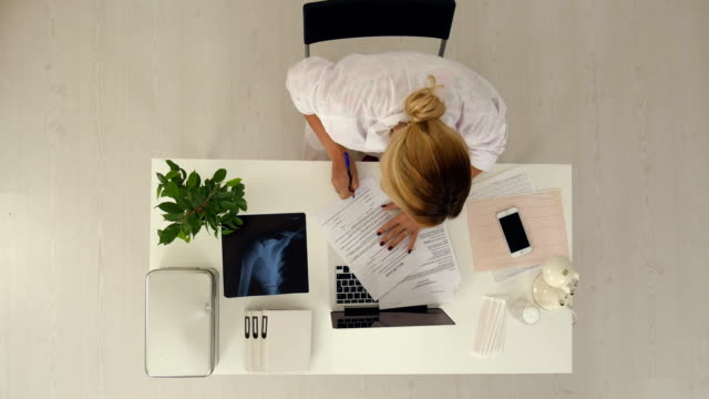 Jungen-und-professionellen-Arzt-arbeitet-mit-vielen-Dokumente-in-office